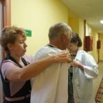Ольга Кудленко помогает надеть халат Александру Якимову